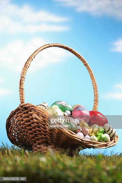 Basket filled with Easter eggs on grass, ground view (focus on basket)