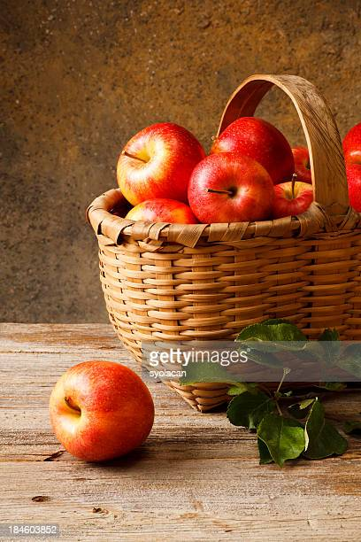 Basket full of red apples on a wooden surface
