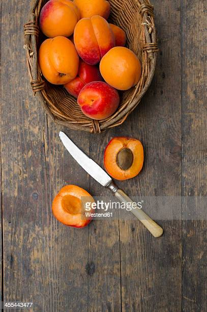 Basket of apricots with knife on wooden table, close up