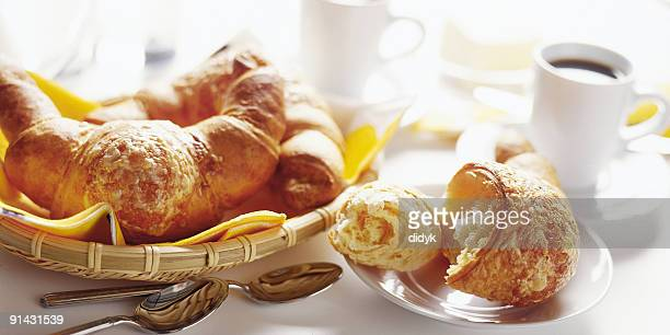 Basket of breakfast croissants with black coffee
