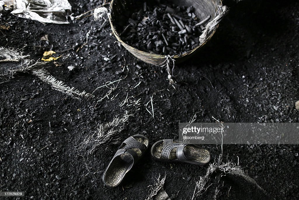 A basket of coal and a pair of sandals sit on the ground at a coal wholesale market in Mumbai, India, on Tuesday, July 2, 2013. India, the worlds third-largest coal consumer, imported 43 percent more of the fuel than a year ago on increased demand from power stations and steelmakers, according to shipping data, and is set to eclipse China as the top importer of power station coal by 2014. Photographer: Dhiraj Singh/Bloomberg via Getty Images