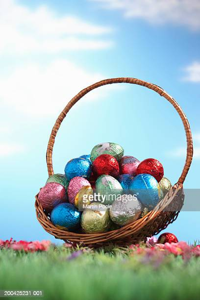 Basket of foil wrapped Easter eggs on grass