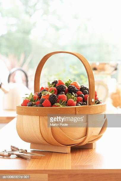 Basket of fresh raspberries and blackberries on kitchen counter