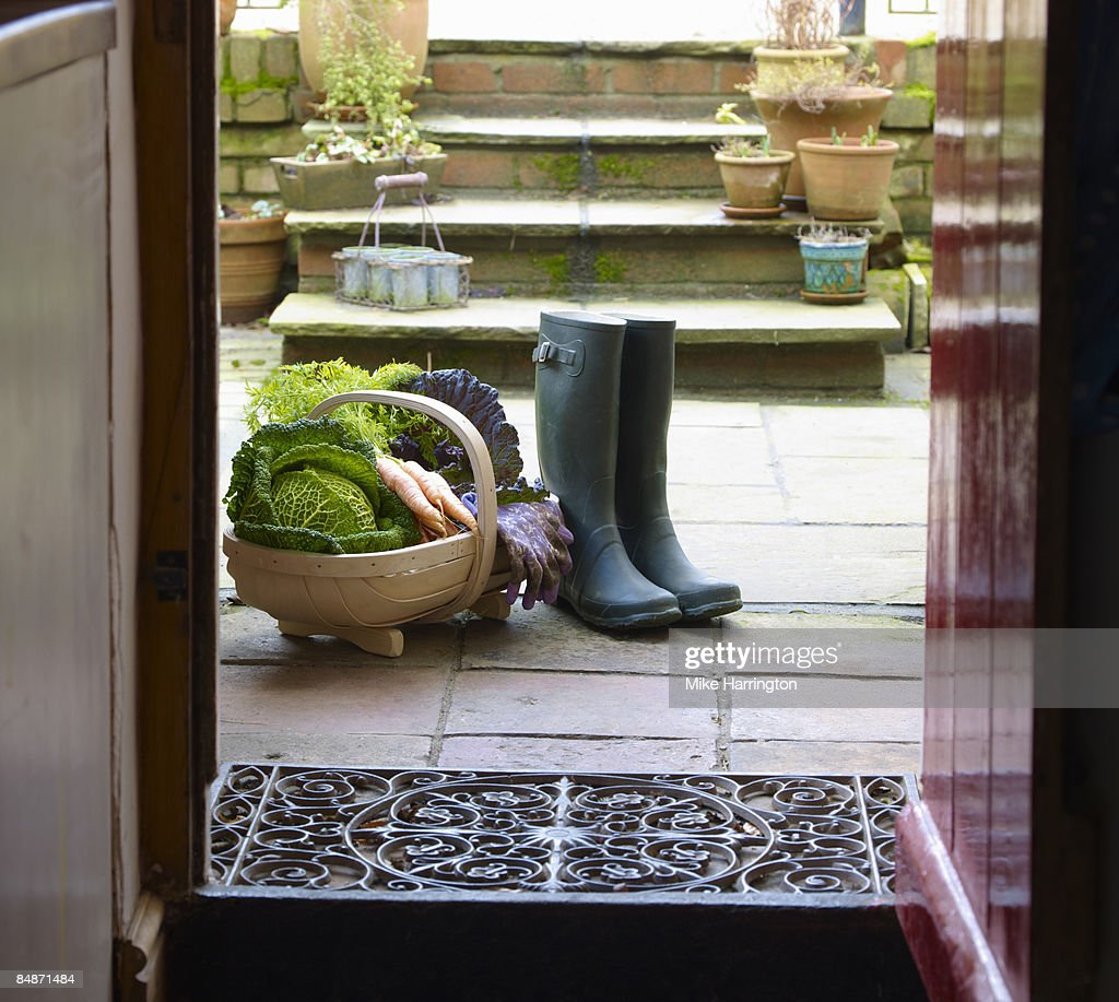Basket of organic vegetables and boots at door