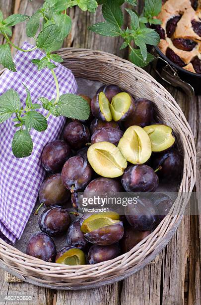 Basket of prunes with prune cake on wooden table, close up