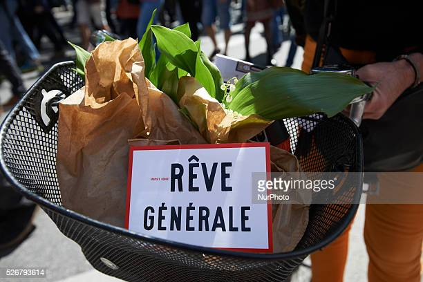 A basket on a bicycle with Lily of the Valley with a sticker reading 'General Dream' a play on the French words 'Gr��ve' ie strike and R��ve ie Dream...