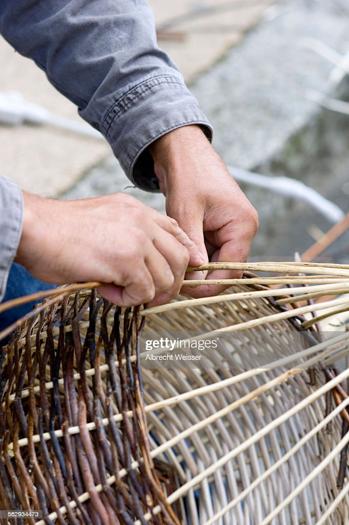 A basket weaver sitting on the street and weaving a basket, Brittany, France, Europe