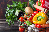Basket with assortment of fresh vegetables on a wooden rustic background