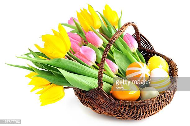 Basket with bunch pink yellow tulips and eggs white background
