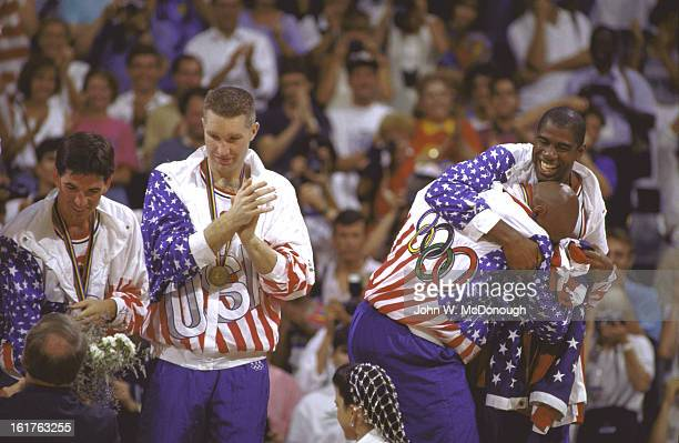 1992 Summer Olympics USA John Stockton Chris Mullin Charles Barkley and Magic Johnson victorious on medal stand after winning Men's Gold Medal game...