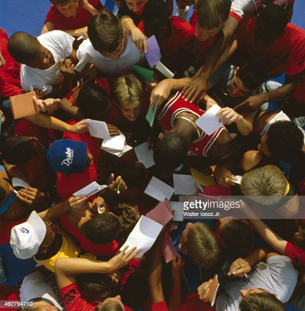 Aerial portrait of Chicago Bulls Michael Jordan surrounded by youth fans seeking autographs during photo shoot at Illinois Benedictine College Lisle...