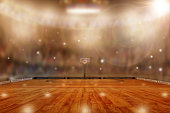 Low angle view of fictitious basketball arena with flashes from sports fans in the stands and lens flare effect. Focus on foreground with deliberate shallow depth of field on background and copy space