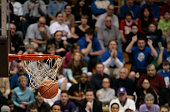 Basketball ball and backboard with fans in the background.
