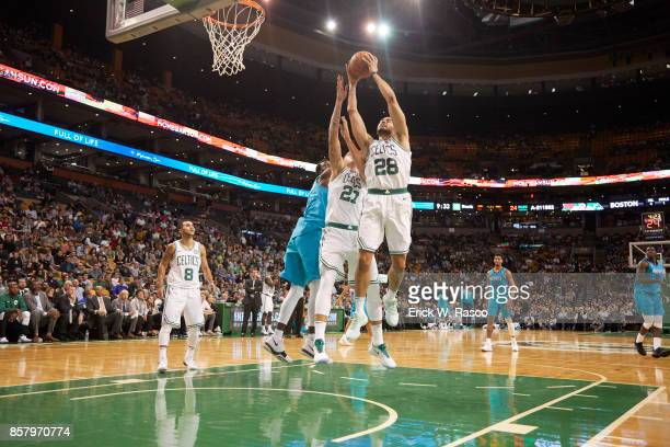Boston Celtics Abdel Nader and Daniel Theis in action rebounding vs Charlotte Hornets during preseason game at TD Garden Boston MA CREDIT Erick W...
