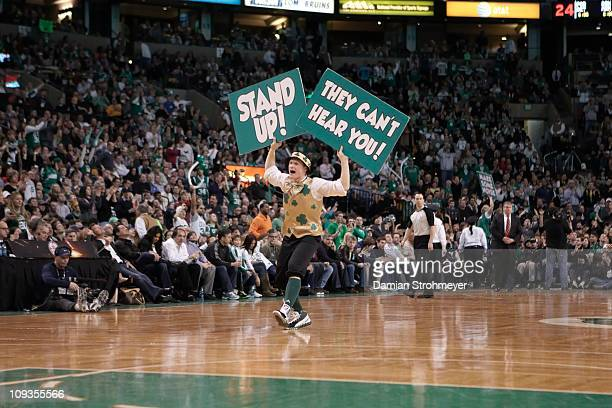 Boston Celtics Lucky the Leprechaun mascot on court with STAND UP and THEY CAN'T HEAR YOU signs during game vs Miami Heat at TD GardenBoston MA...