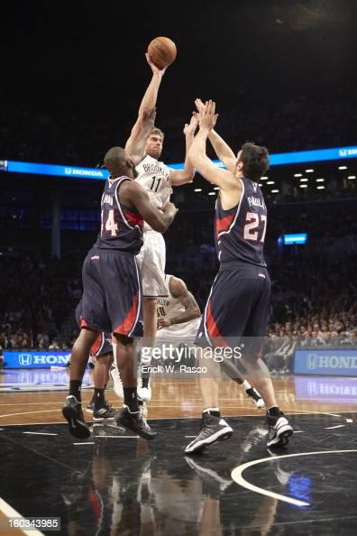 Brooklyn Nets Brook Lopez in action vs Atlanta Hawks Zaza Pachulia and Ivan Johnson at Barclays Center Brooklyn NY CREDIT Erick W Rasco