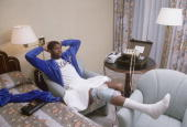 Casual portrait of Los Angeles Lakers Magic Johnson icing down sore knee in Hilton Hotel room of trainer Gary Vitti after practice and before game vs...