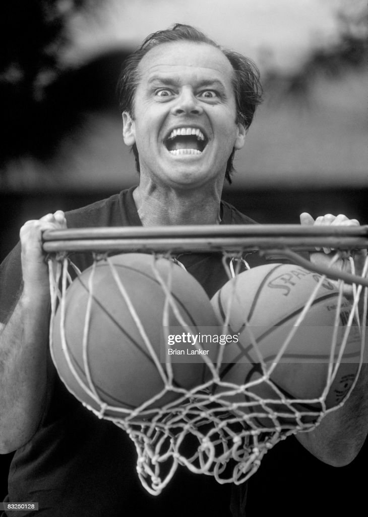 Closeup portrait of celebrity actor and Los Angeles Lakers fan Jack Nicholson dunking ball into net.