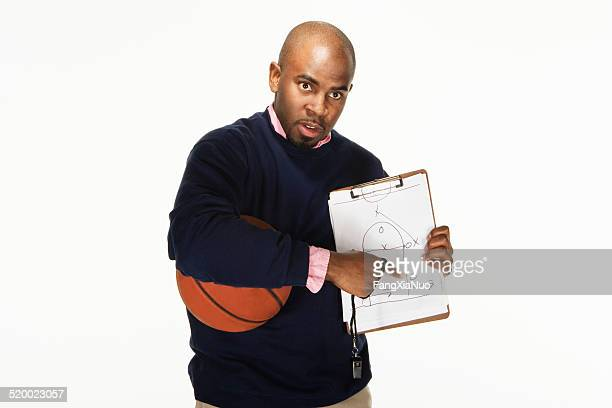 Basketball coach giving play instructions, on white background