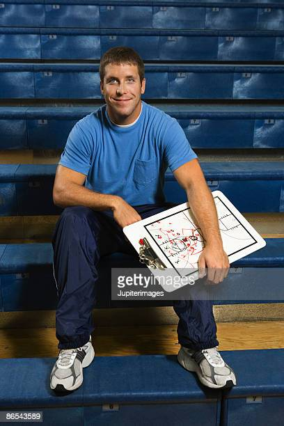 Basketball coach sitting on bleachers