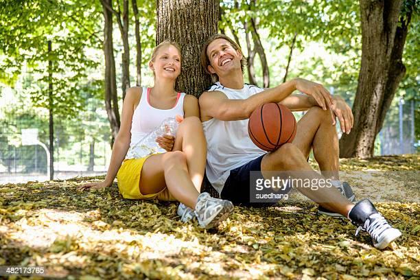 Basketball couple taking a break in park