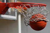 A basketball falls through a basket
