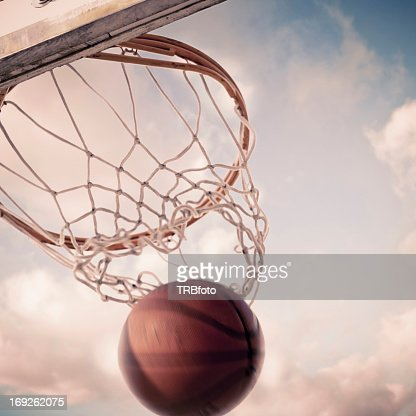 Basketball falling through hoop on court