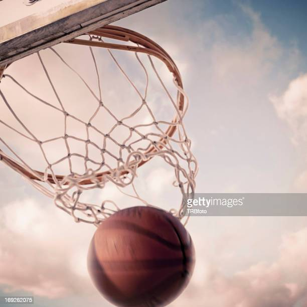 Basketball falling through hoop on court