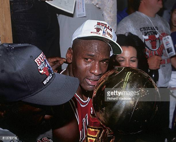 Basketball finals Closeup of Chicago Bulls Michael Jordan victorious with wife Juanita and trophy after game vs Los Angeles Lakers Los Angeles CA...