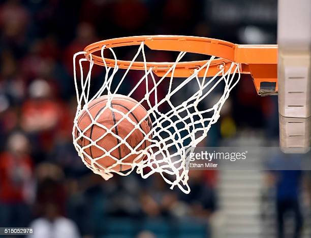 A basketball goes through a hoop and net before a semifinal game of the Pac12 Basketball Tournament between the Arizona Wildcats and the Oregon Ducks...