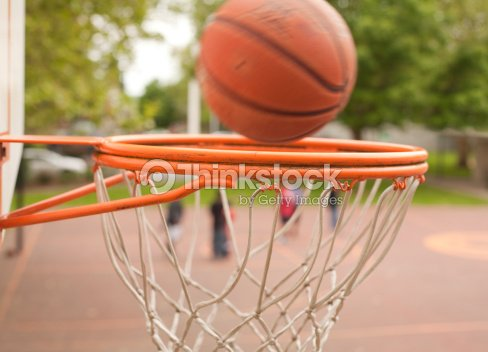 basketball going into basket at outdoor court stock photo thinkstock