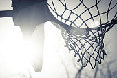 A close up of a basketball hoop with the sun shining through it.