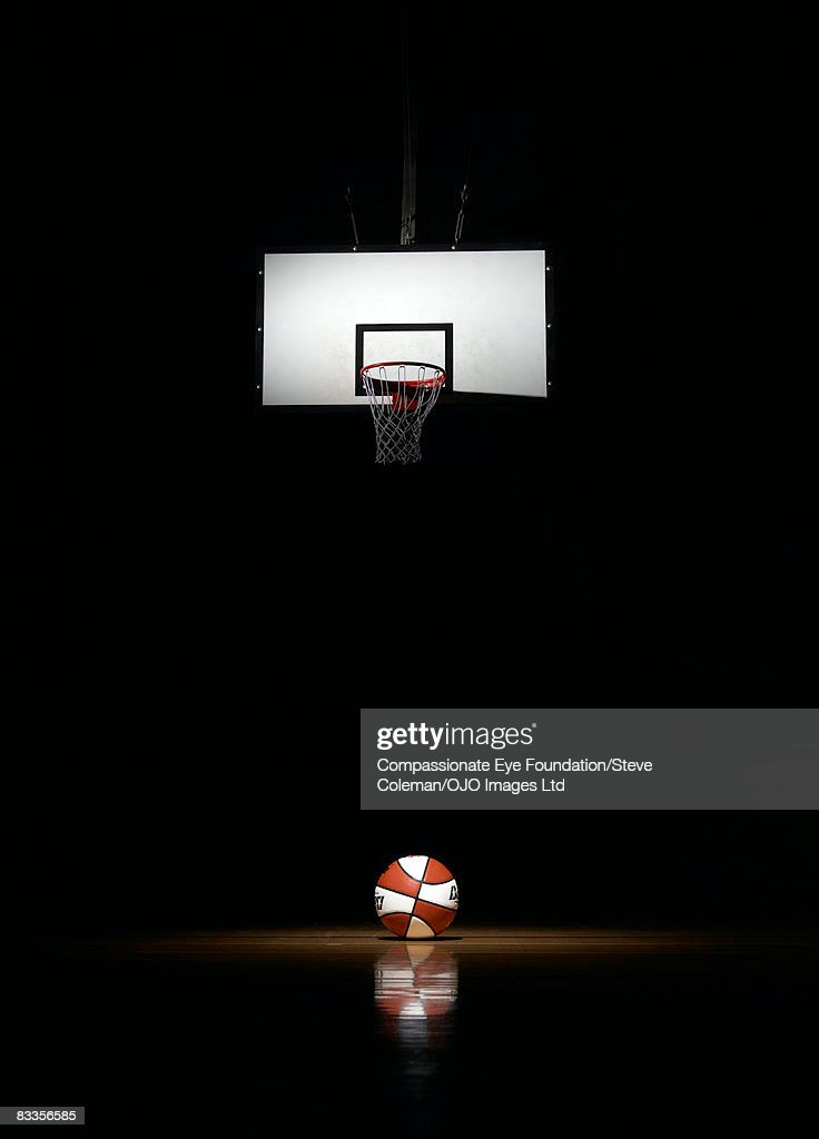 Basketball in the spotlight, underneath the basket