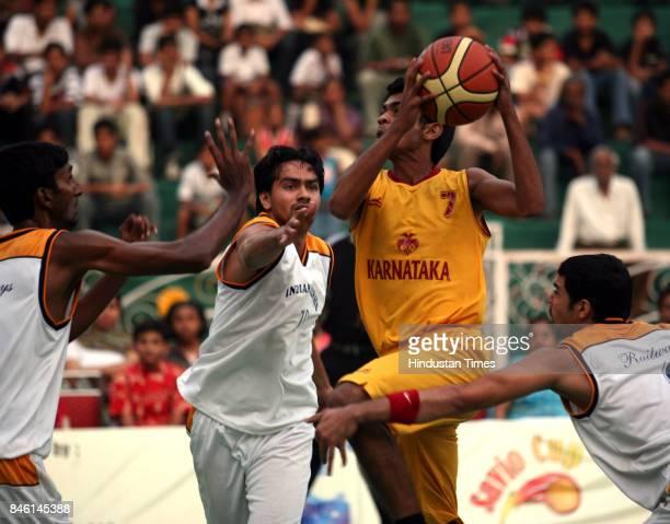Basketball Indian Railway vs Karnataka Indian Railways players try to block a Karnataka forward during a Savio Cup basketball match at Don Bosco High...