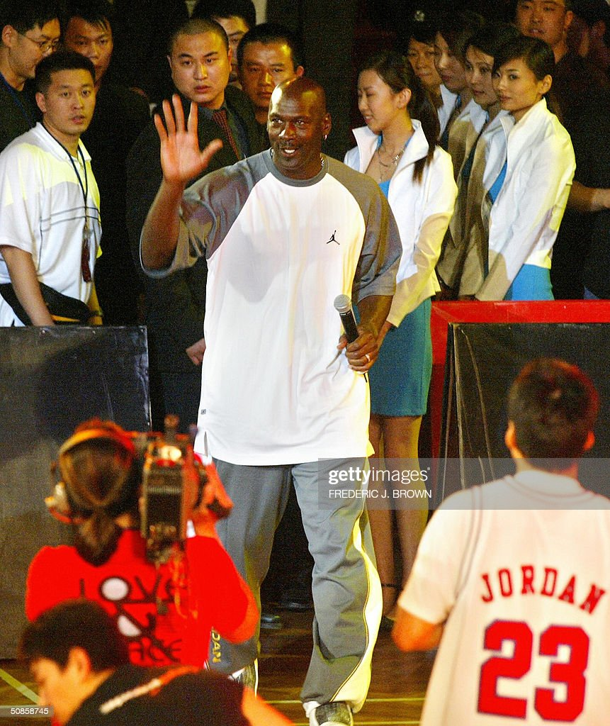 US basketball legend Michael Jordan waves to the crowd as he arrives for a presentation ceremony for China's High School championship, 20 May 2004, at the Worker's Stadium Gymnasium in Beijing. Despite being a no show at open public events in the Chinese capital yesterday, Jordan's slick promotional tour has grabbed more headlines than the return to China of the nation's homegrown NBA hero Yao Ming. Jordan presented the trophy to the winning team from Shenyang's #31 High School, which defeated Shanghai's Nanyang Model High School. AFP PHOTO/Frederic J. BROWN
