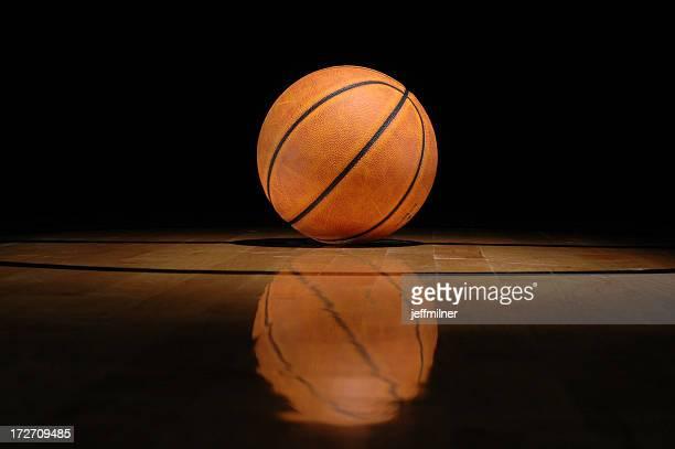 Basketball lying on shiny court against black background
