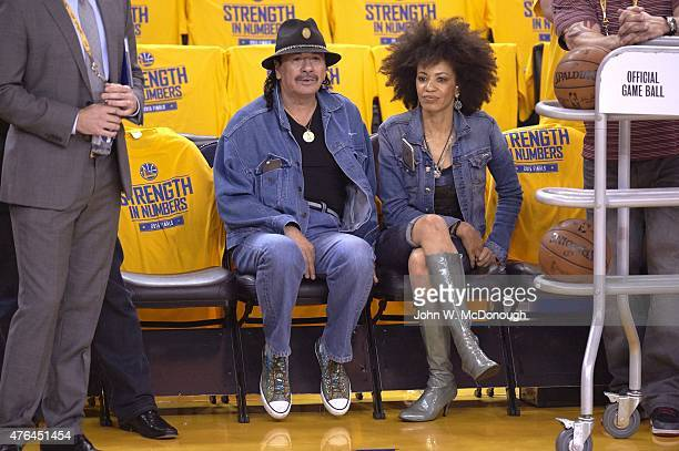 NBA Finals Celebrity guitarist Carlos Santana with wife Cindy Blackman Santana sitting courtside before performing anthem and before Golden State...