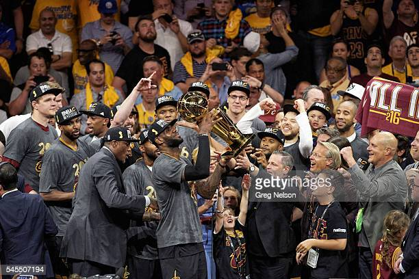 NBA Finals Cleveland Cavaliers LeBron James victorious holding up Larry O'Brien trophy with team owner Dan Gilbert and teammates looking on after...