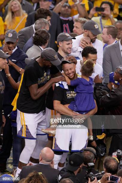 NBA Finals Golden State Warriors Stephen Curry holding daughter as Kevin Durant fools around with Curry after winning game and series vs Cleveland...