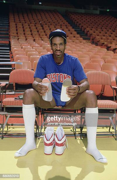 NBA Finals Portrait of Detroit Pistons Adrian Dantley sitting on bench holding his insoles in hands before game vs Los Angeles Lakers at Pontiac...