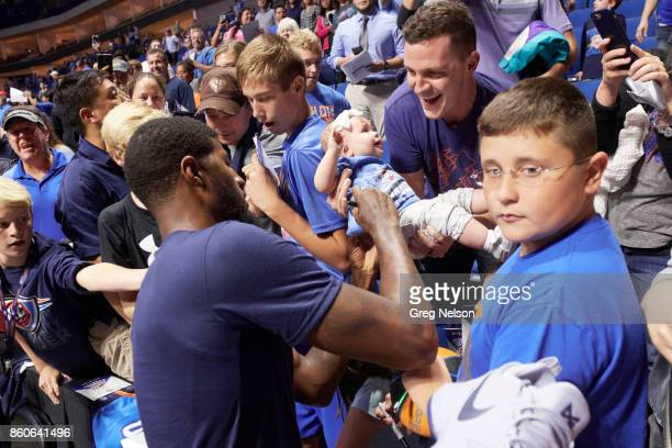 Oklahoma City Thunder Paul George signing autograph on young fan's tee shirt in stands before preseason game vs Houston Rockets at BOK Center Goofy...