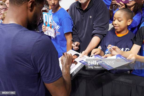 Oklahoma City Thunder Paul George signing autographs for young fan in stands before preseason game vs Houston Rockets at BOK Center Tulsa OK CREDIT...