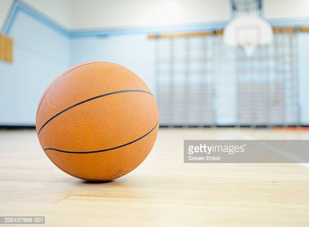 Basketball on floor of school gymnasium (focus on ball in foreground)