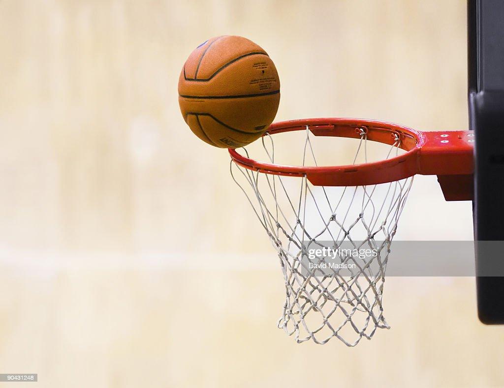 Basketball on rim of basket.