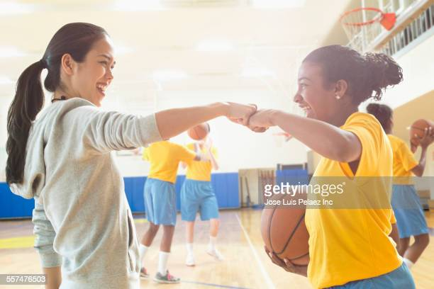 Basketball player and coach fist-bumping during practice
