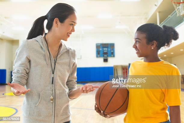 Basketball player and coach talking during practice in gym