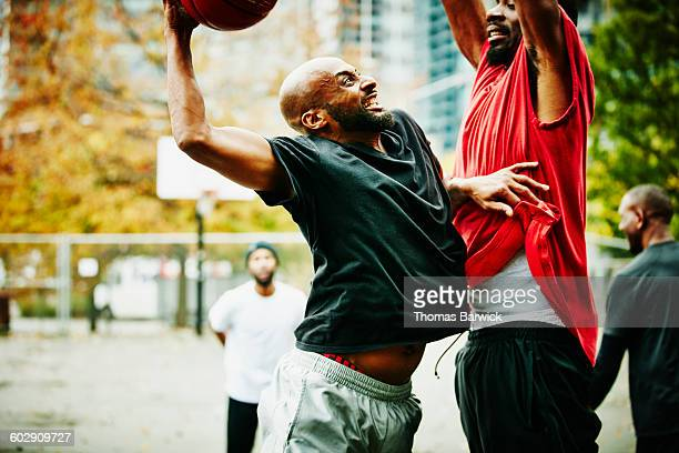 Basketball player attempting to dunk on defender