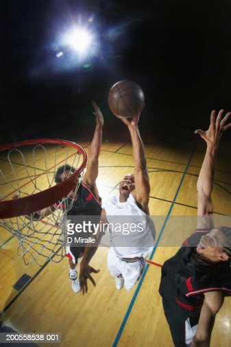Basketball player attempting to slam dunk ball
