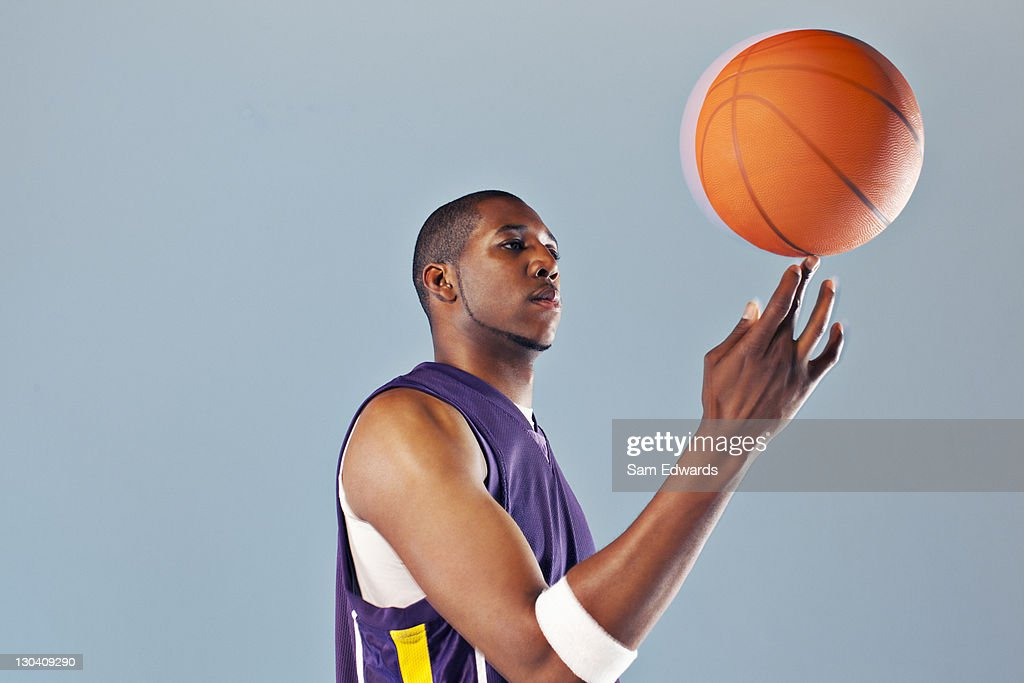 Basketball player balancing ball on one finger : Stock Photo