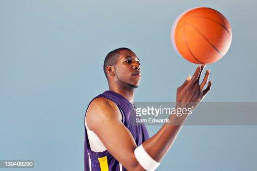 Basketball player balancing ball on one finger : Stock Photo
